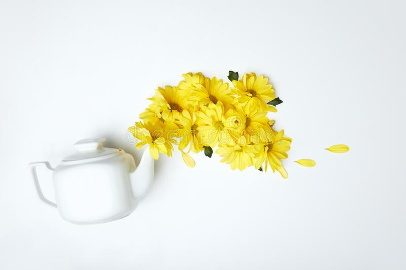 Pouring yellow daisies from white teapot isolated on white royalty free stock image