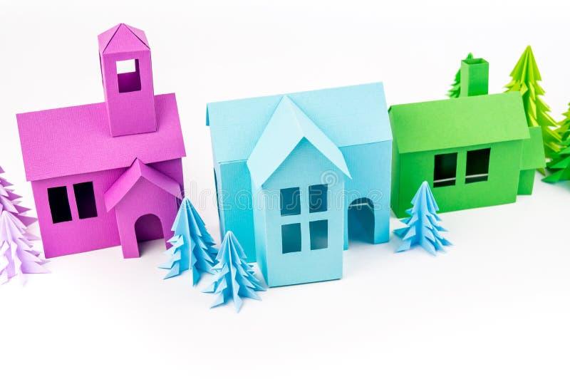 Pourpre et maison verte bleue collés hors des supports de papier dans la forêt violette photographie stock