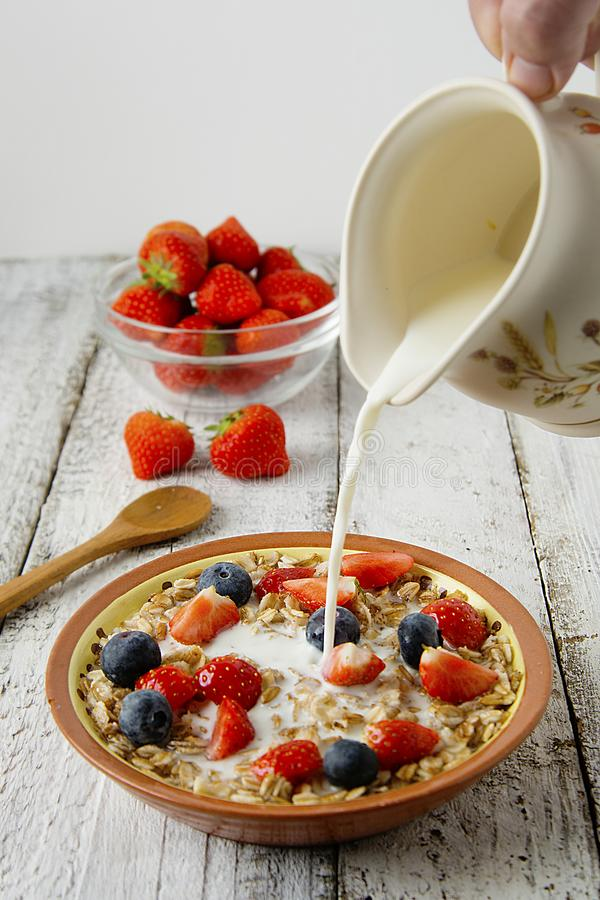Pourring Milk over Healthy Homemade Oatmeal with Berries - fresh strwberries and blueberries, for Breakfast. Rustic white wooden stock images