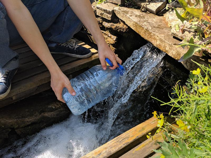 Pours water into a bottle from stream with clean drinking water.  royalty free stock images