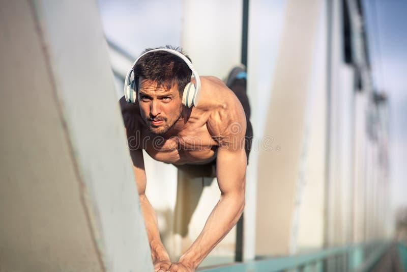 Pousées d'homme de forme physique de sport L'exercice masculin d'athlète soulèvent des sorties photographie stock