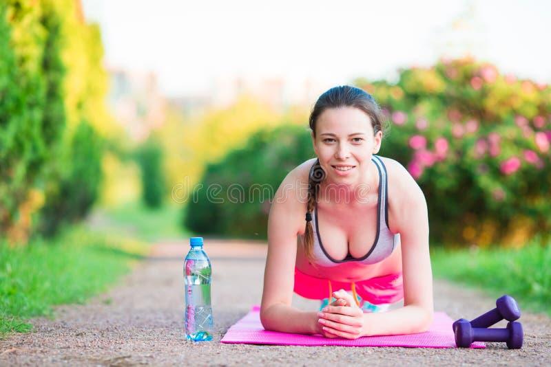 Pousées de formation de fille de forme physique de sport L'exercice d'athlète féminin enfoncent dehors le parc vide Modèle conven photographie stock