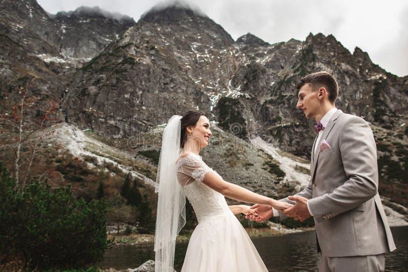 ?pousant des couples marchant et tenant des mains sur le rivage de lac Jour ensoleill? en montagnes de Tatra photos libres de droits