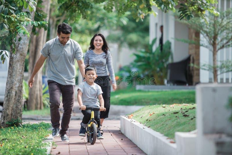Poussée de bicyclette de tour d'enfants par son père photo libre de droits