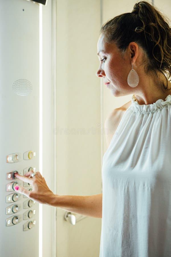 Poussée de femme adulte le bouton à l'intérieur d'un ascenseur photo libre de droits