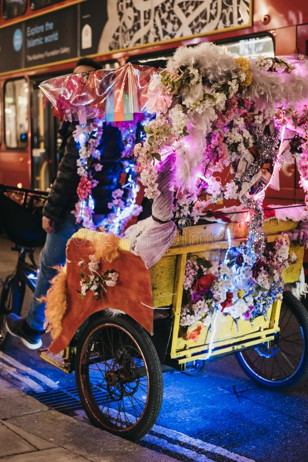 Pousse-pousse colorés décorés des fleurs sur Oxford Street, Londres, R-U, la nuit photographie stock