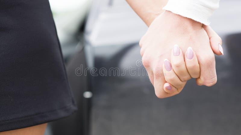 Pousse de concept de l'amitié et de l'amour de l'homme et de la femme - tenir des mains photographie stock libre de droits