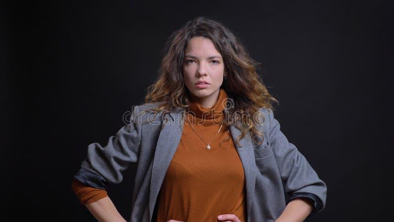 Pousse de plan rapproché de la jeune femme d'affaires caucasienne attirante étant fâchée et ayant ses mains sur des hanches regar photo libre de droits