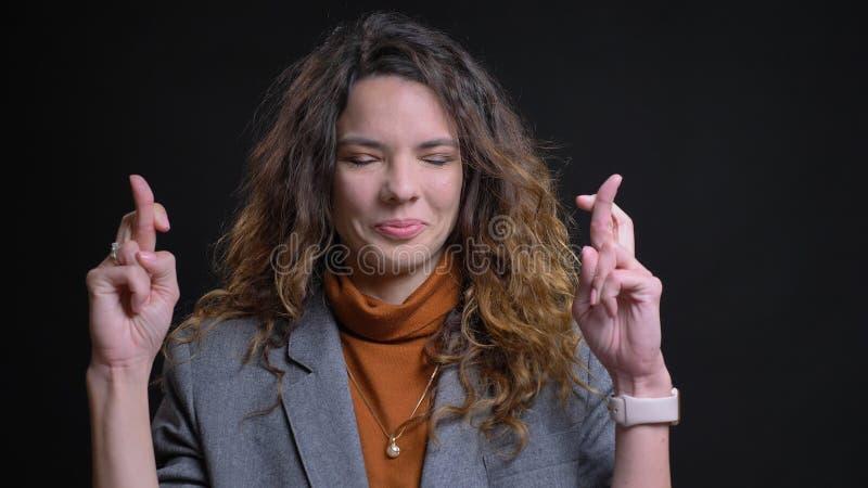 Pousse de plan rapproché de la jeune femme d'affaires caucasienne attirante faisant croiser ses doigts dans l'inquiétude devant l photographie stock
