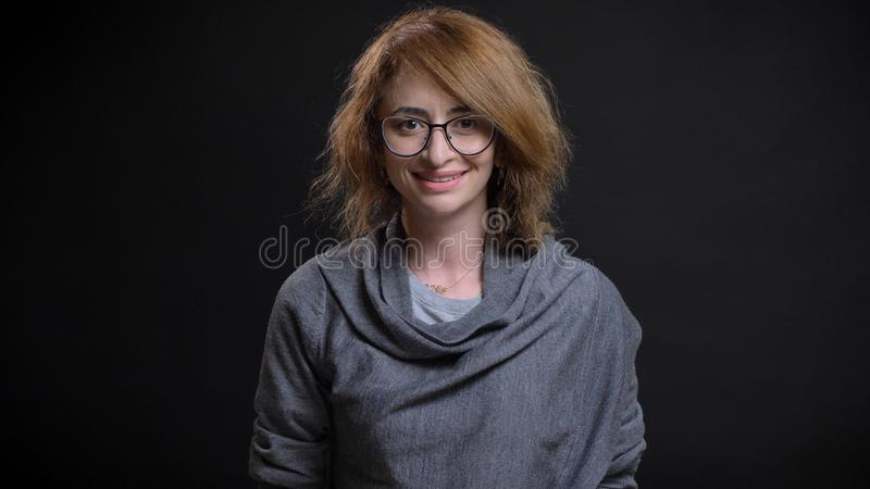 Pousse de plan rapproché de milieu âgée pour lire la femelle caucasienne d'une chevelure en verres souriant heureusement tout en  image libre de droits
