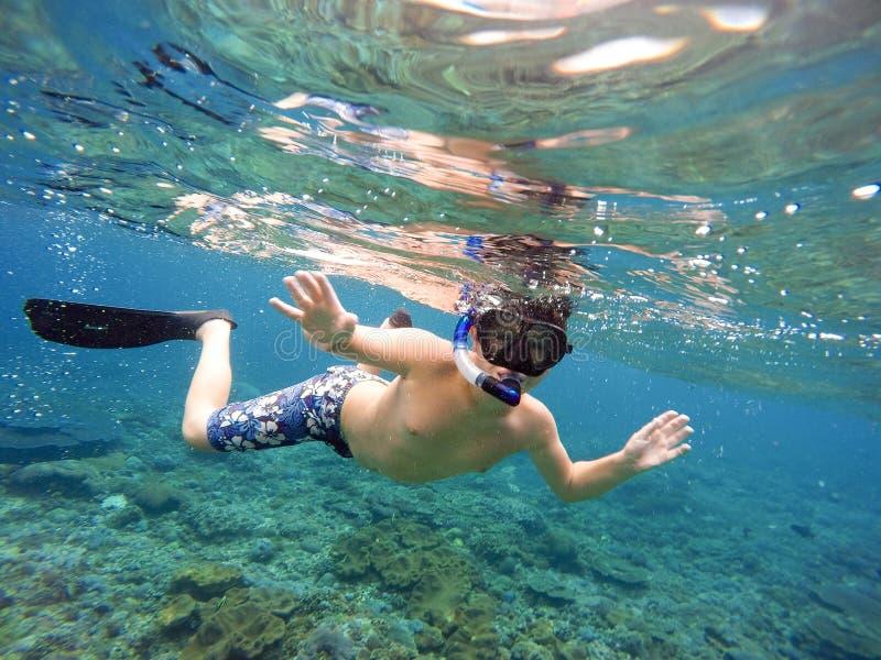 Pousse sous-marine d'un jeune garçon naviguant au schnorchel image libre de droits