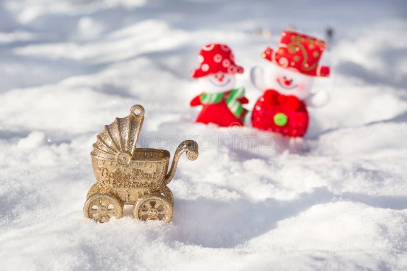 Poussette de nouvelle année avec un nouveau-né sur un fond d'une paire de bonhommes de neige heureux photo libre de droits