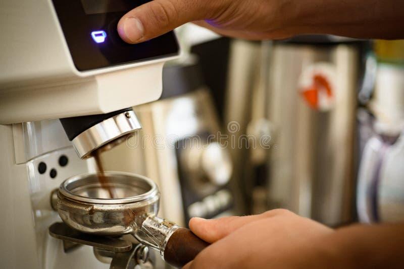 Poussez juste le bouton Cafè moulu frais dans le portafilter Grains de café de morcellement de barman utilisant la machine de caf photographie stock