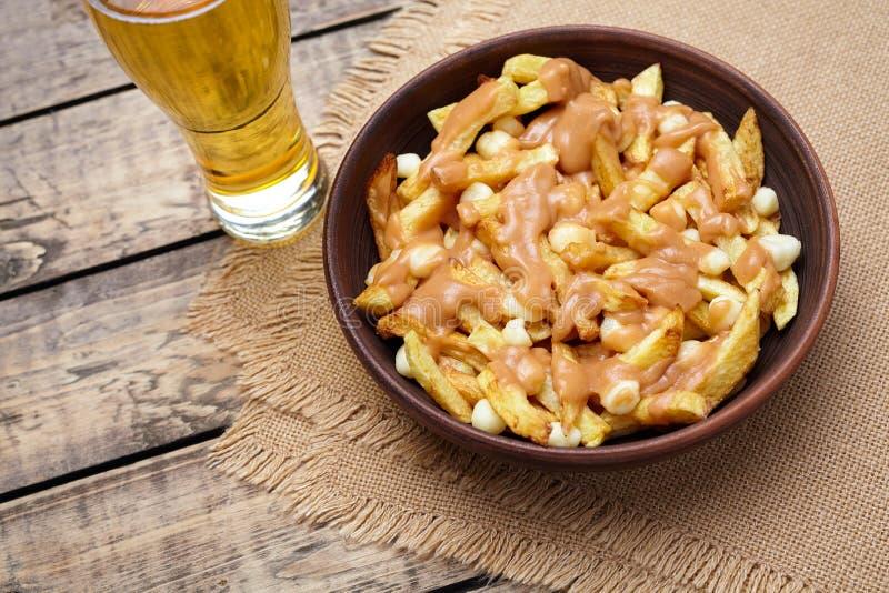Poutine Canadese maaltijd met gebraden gerechten, kwark, bier en jus stock afbeeldingen