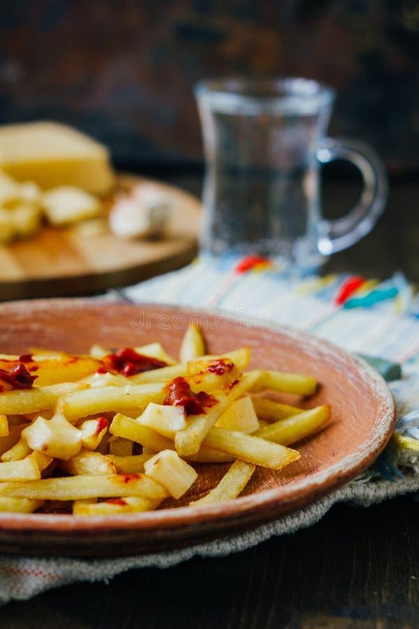 Poutine dłoniaki na czerni powierzchni Kanadyjski naczynie z grulami, serem i kumberlandem, zdjęcie stock
