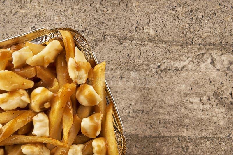 Poutine em um recipiente para viagem Cozinhado com batatas fritas, molho da carne e queijo de coalho foto de stock royalty free