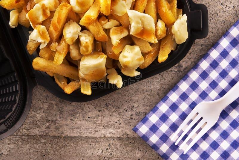 Poutine em um recipiente para viagem Cozinhado com batatas fritas, molho da carne e queijo de coalho imagens de stock