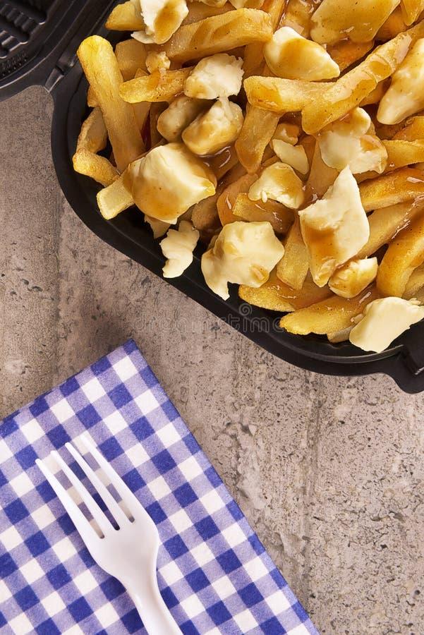 Poutine em um recipiente para viagem Cozinhado com batatas fritas, molho da carne e queijo de coalho foto de stock