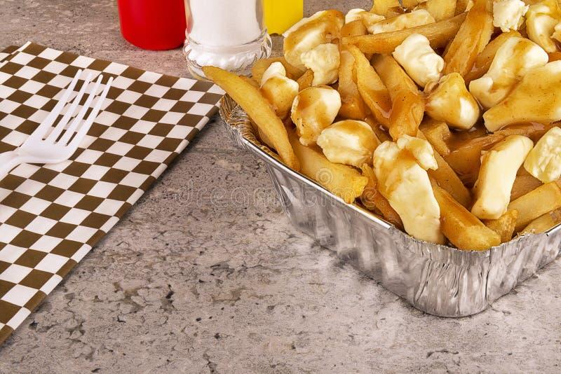 Poutine em um recipiente para viagem Cozinhado com queijo das batatas fritas, do molho e de coalho imagem de stock