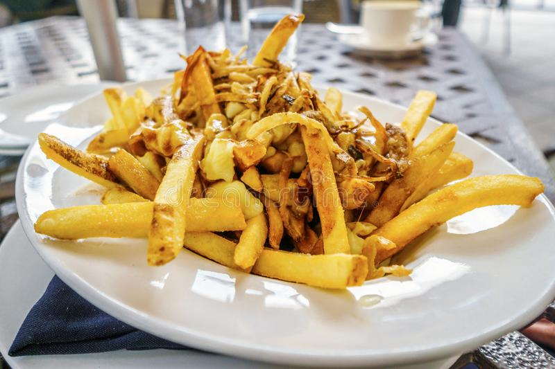 Poutine fries served on white plate stock photography