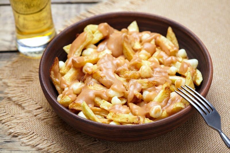Poutine Quebec tradycyjny posiłek z dłoniakami, curd serem i sosem, zdjęcie stock
