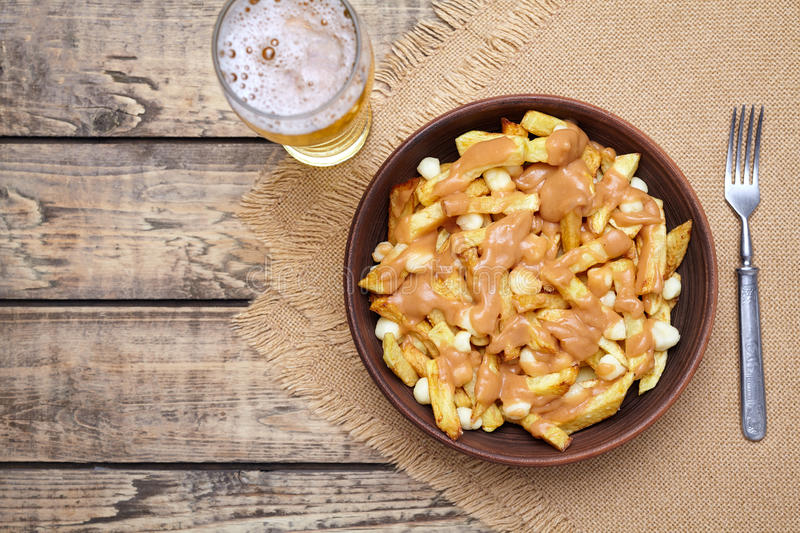 Poutine traditional Canadian meal with fries, curd cheese, beer, sauce royalty free stock image