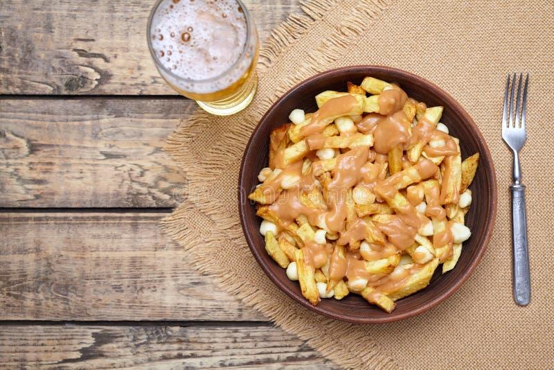 Poutine tradycyjny Kanadyjski posiłek z dłoniakami, curd ser, piwo, kumberland obraz royalty free