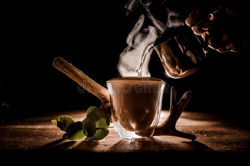 Pouting water into glass cup of coffee. Pouring water into glass cup of coffee with steam from it near plant decor located on the wooden table royalty free stock photos