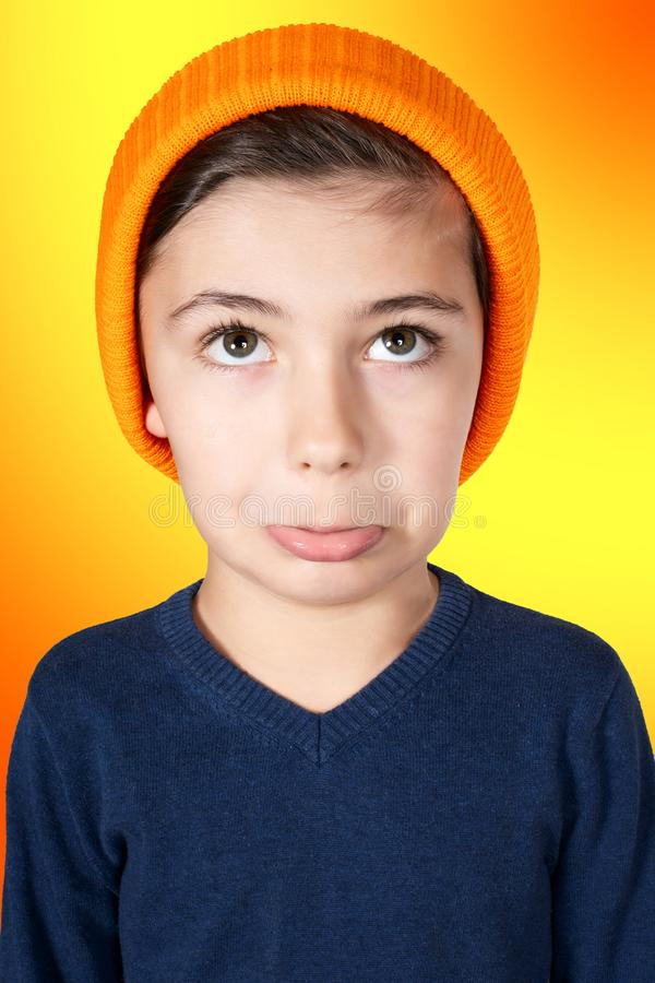 Pouting young boy with big head on orange background stock photos
