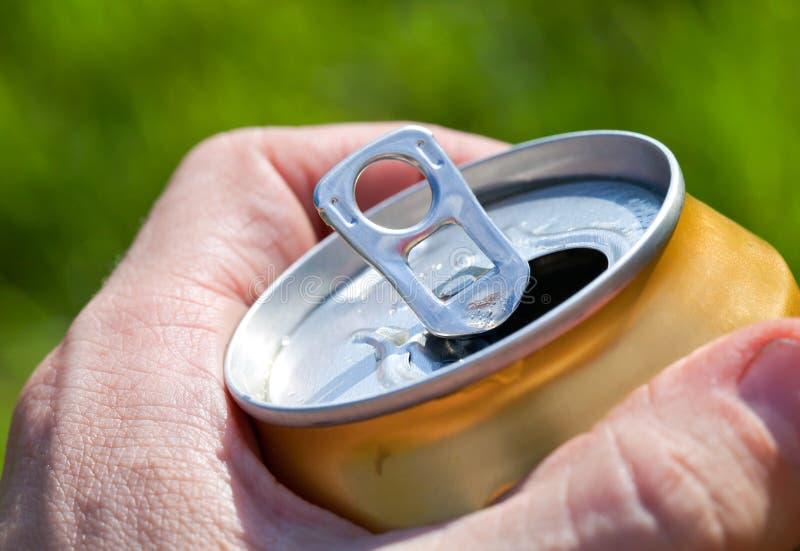 Pouvez de la bière dans la main d'un homme photos stock