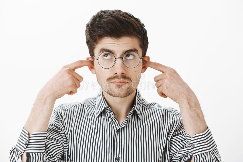 Pouvez vous arrêter la musique svp, j'étudie Le calme a contrarié l'étudiant masculin ringard dans les verres de ballot et la che image stock