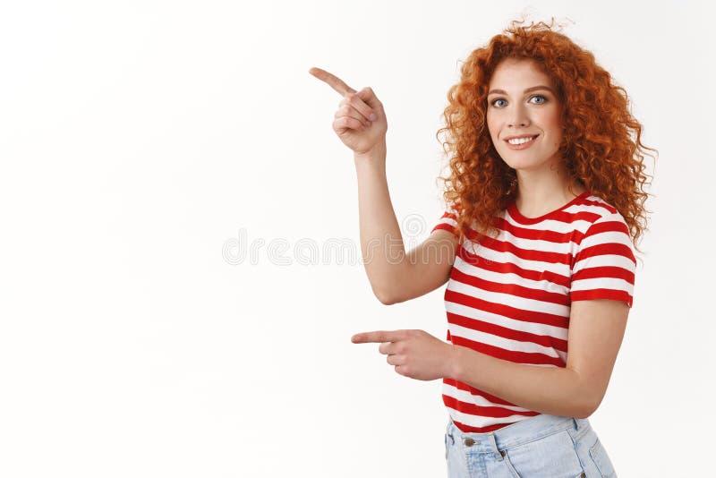 Pouvez vous m'aider à l'obtenir Le T-shirt rayé de femme féminine bouclée rousse belle heureuse dirigeant les index gauches regar photo stock