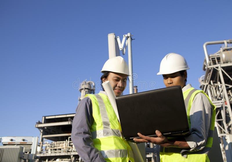 Pouvoir et énergie de deux ingénieurs avec l'ordinateur portable photo stock
