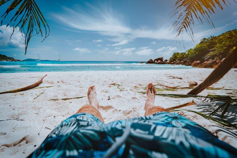 POV снял человека носит голубые плавая шорты кладя на красивый песочный тропический пляж Anse Cosos, Ла Digue, Сейшельские остров стоковая фотография rf
