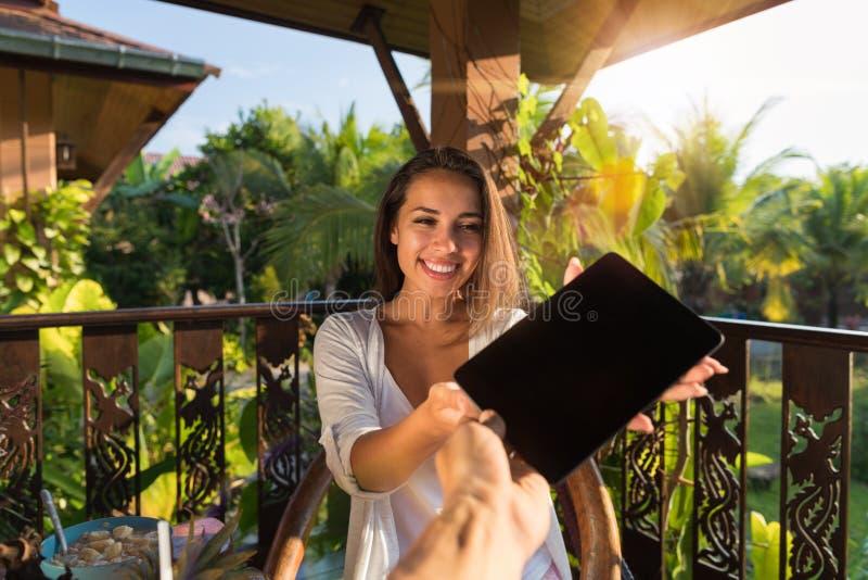Pov человека давая планшет женщины с пустым пустым экраном, красивым ПК цифров владением маленькой девочки сидя Outdoors стоковые изображения rf