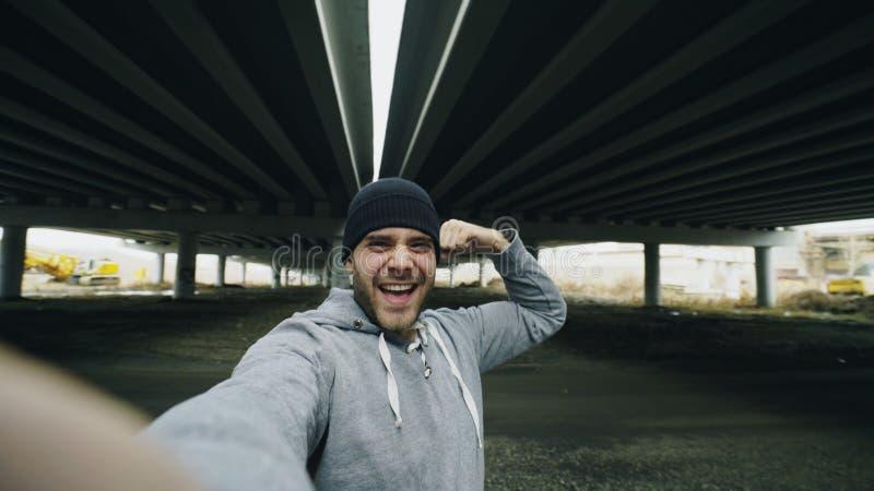 POV av den lyckliga sportive mannen som tar selfieståenden med smartphonen, når utbildning i stads- det frialäge i vinter arkivbild