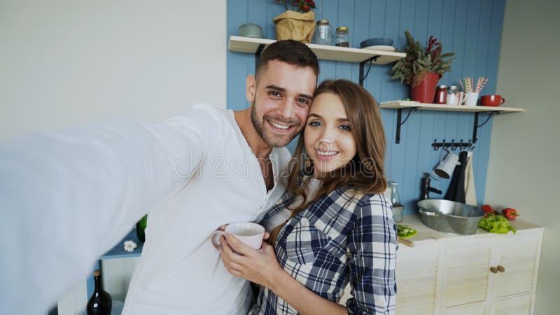POV av unga lyckliga par som tar selfiefoto, medan ha frukosttid i köket hemma royaltyfria foton
