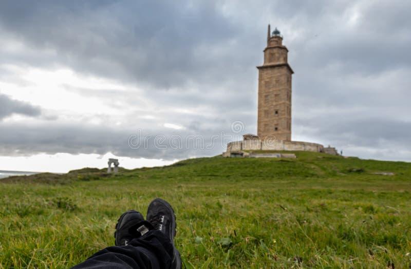 POV che si trova a gambe accavallate sull'erba che guarda un faro di pietra in un Coruña, Galizia, Spagna immagini stock libere da diritti