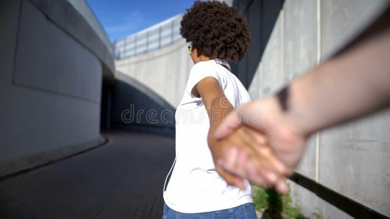 POV des Freundes sch?ner gelockter behaarter Frau folgend, ihre Hand halten, Liebe stockfoto
