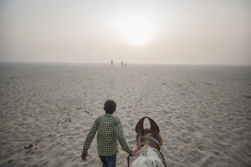 POV montant une avance de cheval par le garçon dans le désert images libres de droits