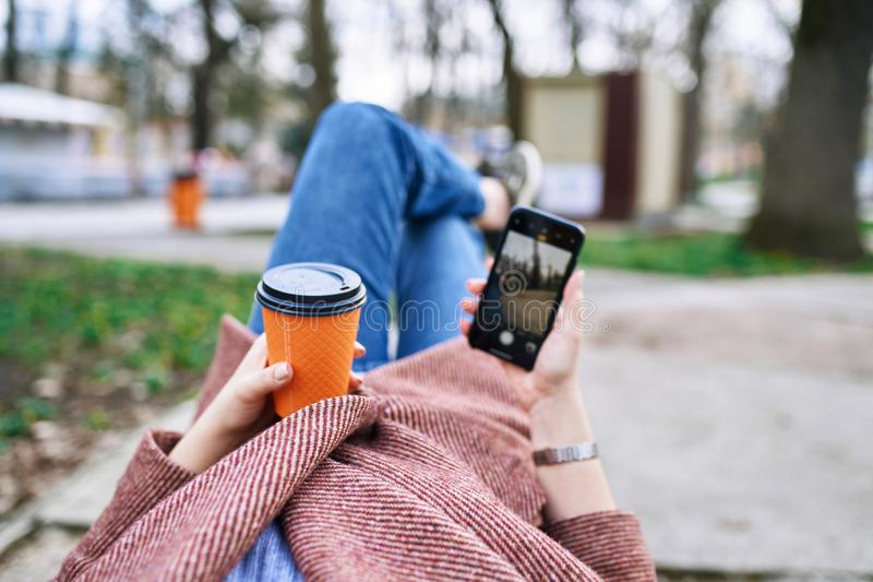 POV pretty woman lying on the bench in spring park and holding mobile phone and orange cardboard cup of tea or coffee. stock photos
