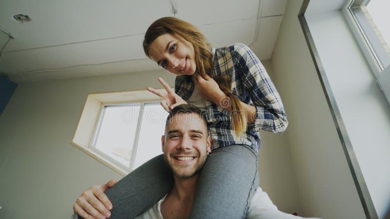 POV van het gelukkige glimlachen en het mooie paar nemen selfie portret op smartphonecamera terwijl meisjeszitting op mensen` s h royalty-vrije stock foto's