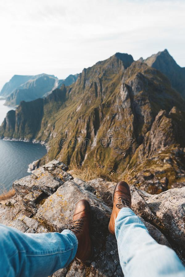 POV view on great mountains and hiking boots. Alone traveler sitting on the edge of mountain above sea. POV view on great mountains and hiking boots stock photo