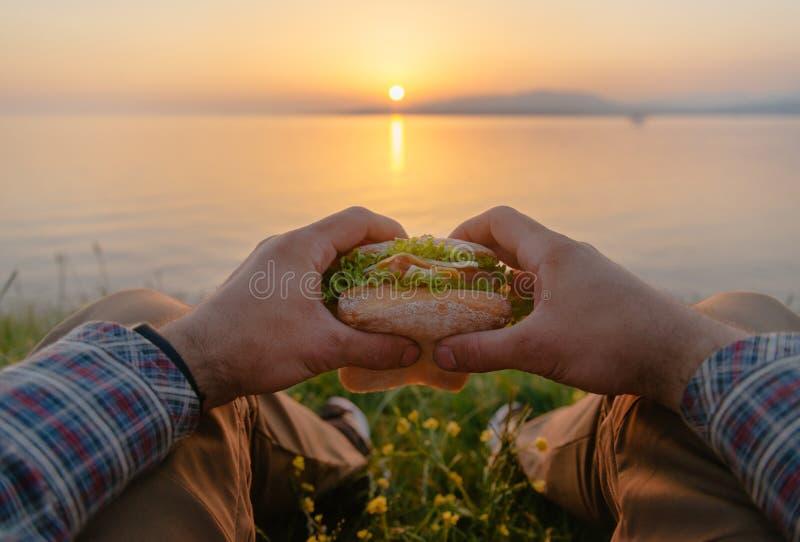 POV wizerunek mężczyzna z hamburgerem morzem przy zmierzchem zdjęcia royalty free
