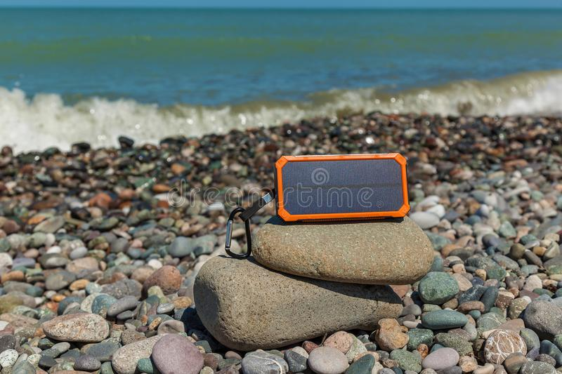 Powerbank charges the phone. The poverbank lies on the pebbles by the sea and charges the phone. Powerbank charges the phone royalty free stock images