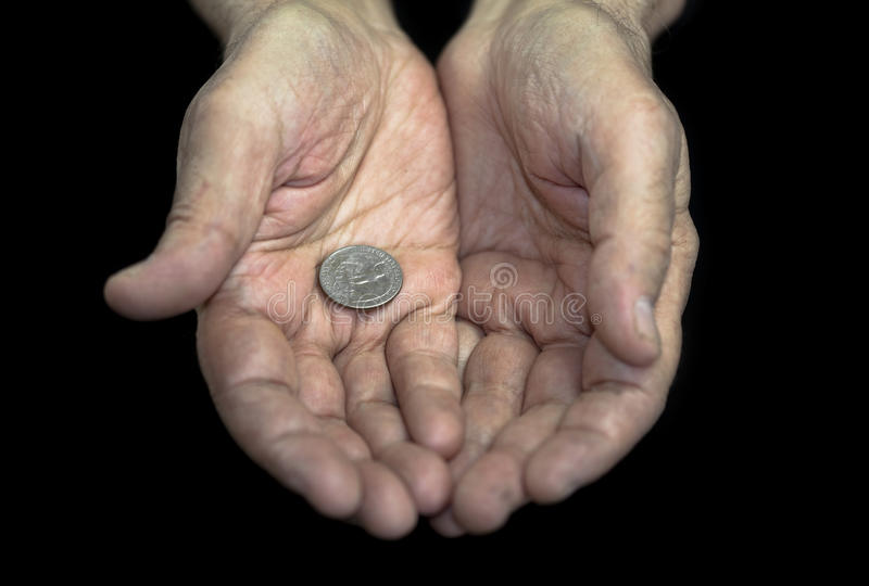 Poverty. Old hands with a single coin of 25 cents royalty free stock image
