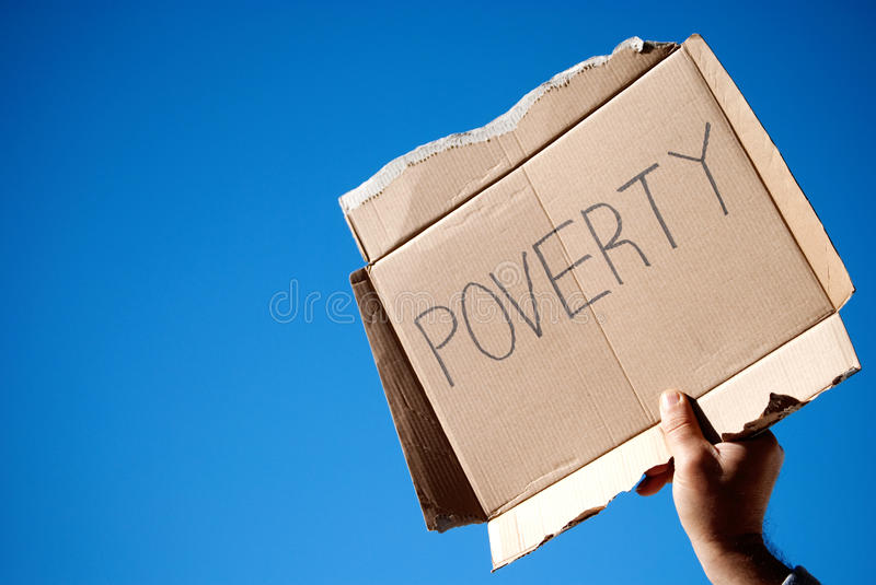 Poverty. Hand holding up on the sky a cardboard sign with the word poverty stock photo