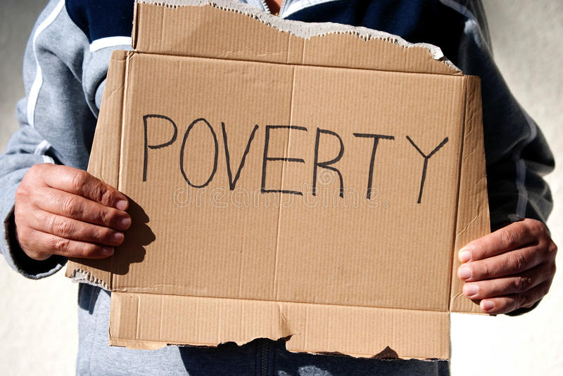 Poverty. Man holding up on a cardboard sign with the word poverty