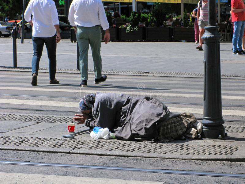 Poverty and begging, old woman. Budapest, Hungary - June 1, 2017: Old woman lies on street near pedestrian crossing. Fingers of her arms are stretched out in stock photos