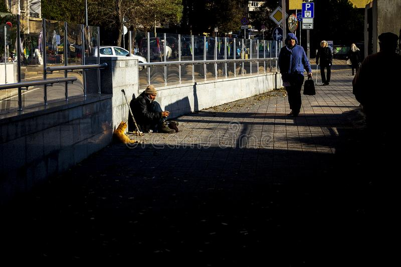A homeless invalid asks for money on the street and his cat makes a company in Burgas/Bulgaria/12.06.2018/ stock image